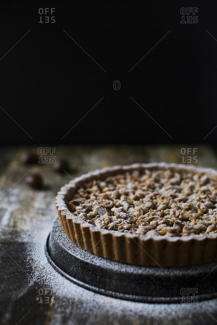 Close up of a gluten free tart with candied apples and walnuts topped with sugar