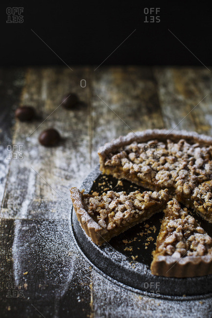 Close up of a sliced gluten free tart with candied apples and walnuts topped with sugar