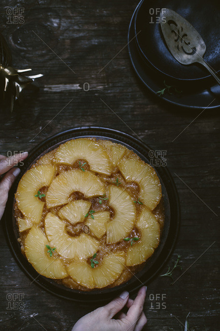 Woman placing a pineapple upside down cake on a reclaimed wood table