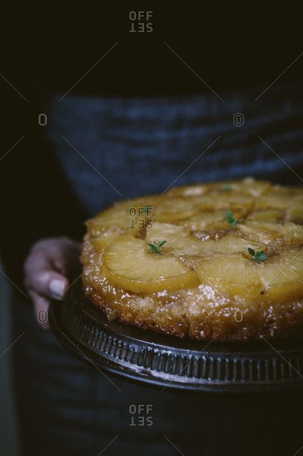 A woman holding a pineapple upside down cake