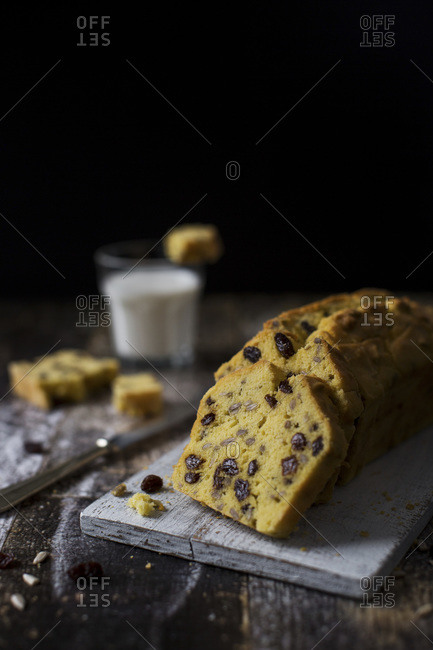 Buttery gluten free cake slices with raisins and sunflower seeds on a cutting board