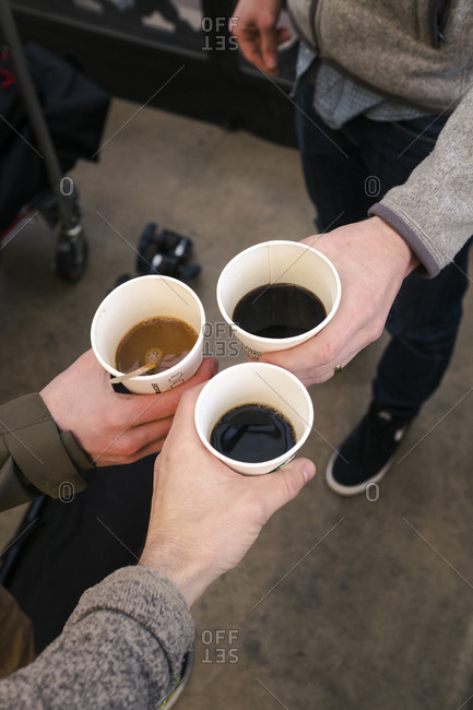 Coffee cups being raised in a toast