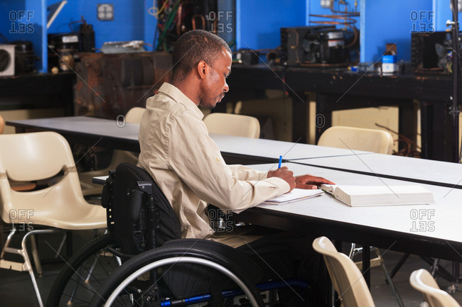 Student in wheelchair taking notes in a lab