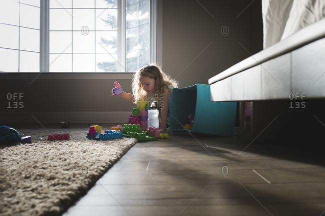 Girl with building blocks in sunlight