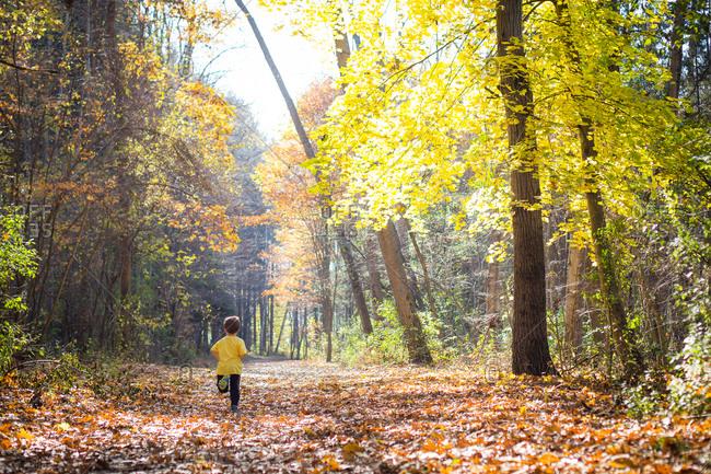 Boy running down a leaf strewn trail in a forest