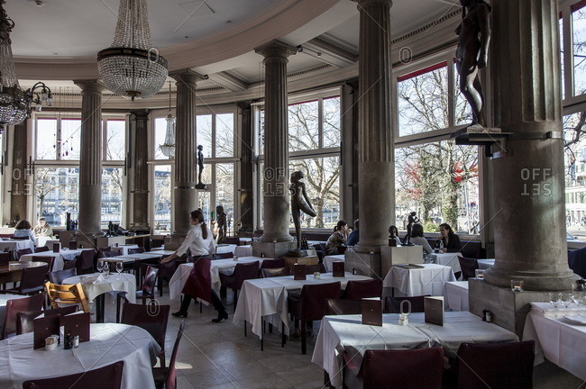 Zurich, Switzerland  - February 21, 2016: Diners in a circular restaurant with interior columns and statues