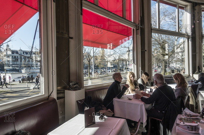 Zurich, Switzerland  - February 21, 2016: People seated at table by window of elegant restaurant in Switzerland