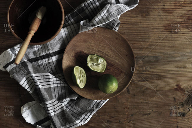 Limes and tea towel on a wooden table