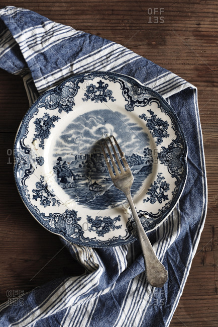 Vintage blue plate and tea towel on a wooden table