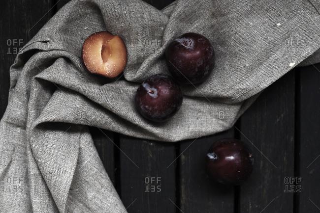 Plums on a gray tea towel