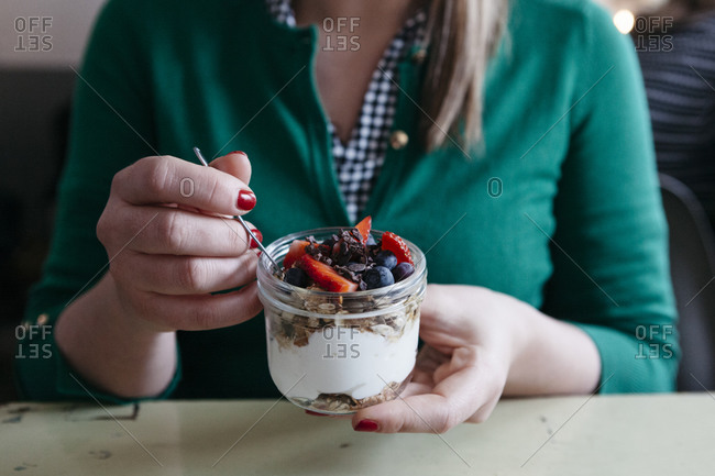 Woman eating granola with yogurt and berries