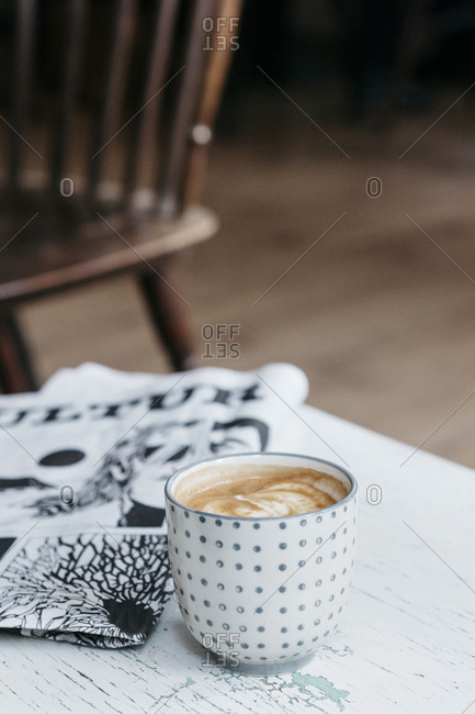 Coffee cup next to a newspaper
