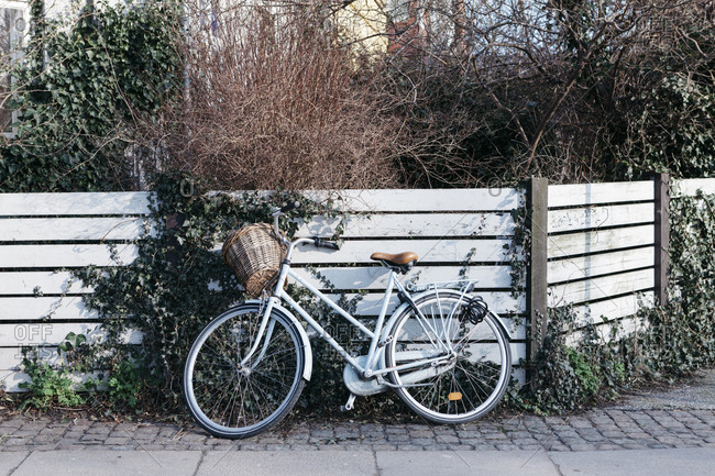 Bicycle leaning against a fence
