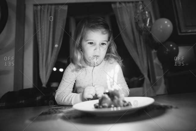 Girl sitting at a table preparing to blow out the candles on her birthday cake