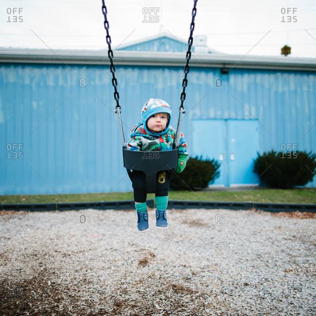 Toddler bundled up in winter clothes and sitting in a swing