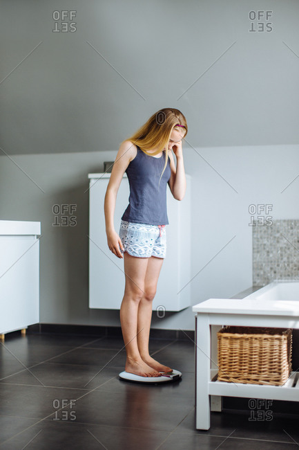 Young girl in bathroom, standing on scales