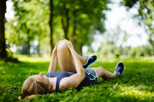 Young girl in park, lying on grass, stretching legs