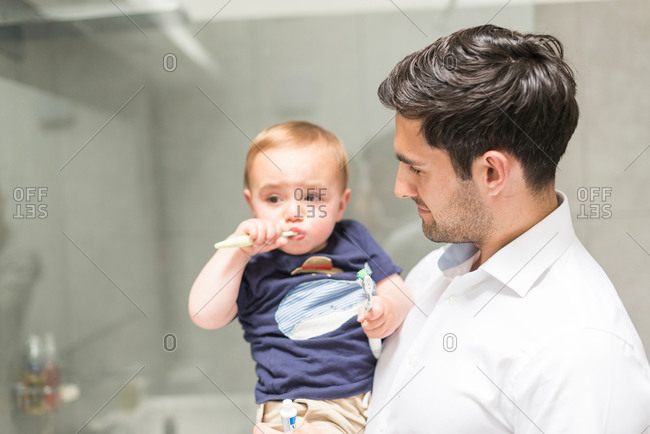 Father holding young son while son brushes teeth