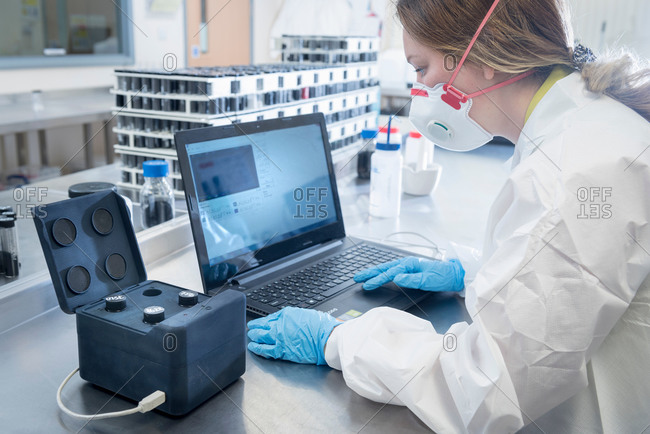 Scientist with dispersion analysis machine in graphene processing factory