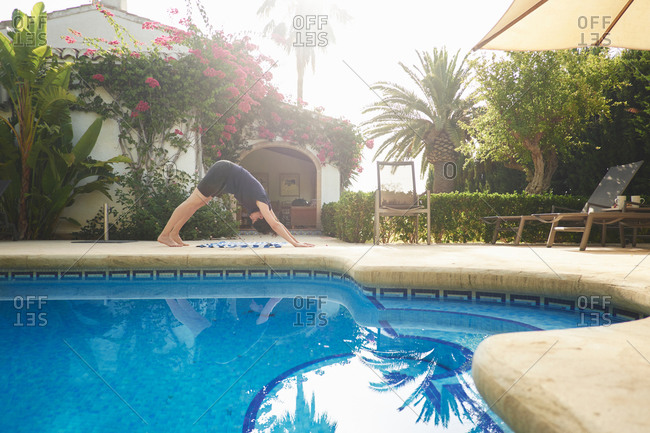Mature woman doing yoga at vacation apartment poolside