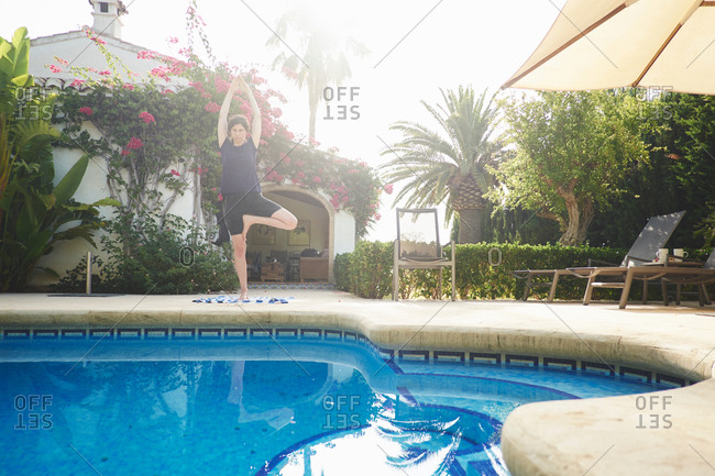 Mature woman in yoga pose at vacation apartment poolside