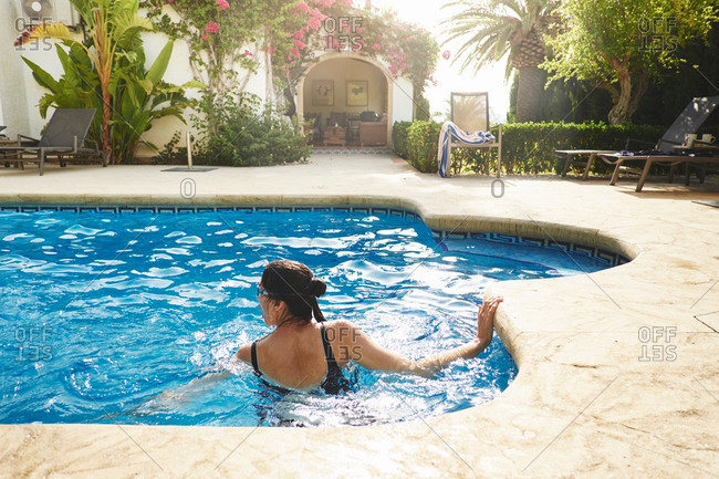 Mature woman swimming in vacation apartment swimming pool
