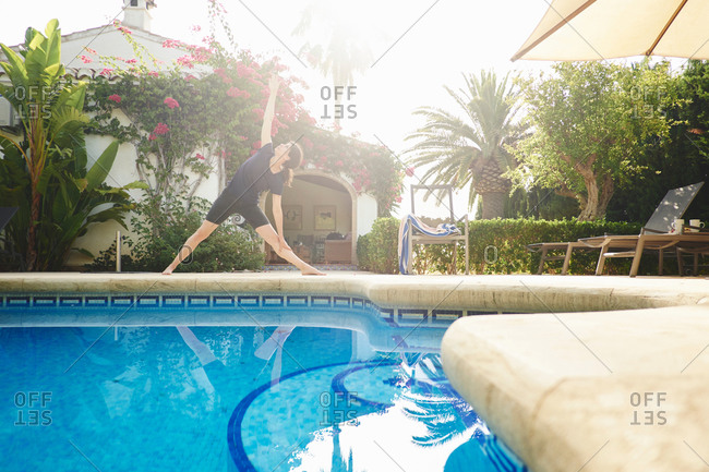 Mature woman doing yoga at poolside vacation apartment