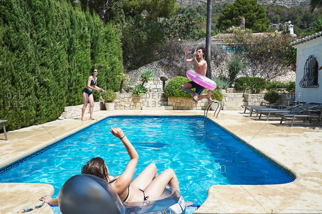Mature woman with son and daughter playing in apartment swimming pool