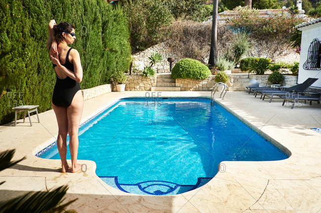 Rear view of mature woman wearing bathing costume standing poolside