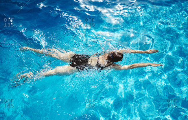 Overhead view of mature woman swimming in swimming pool