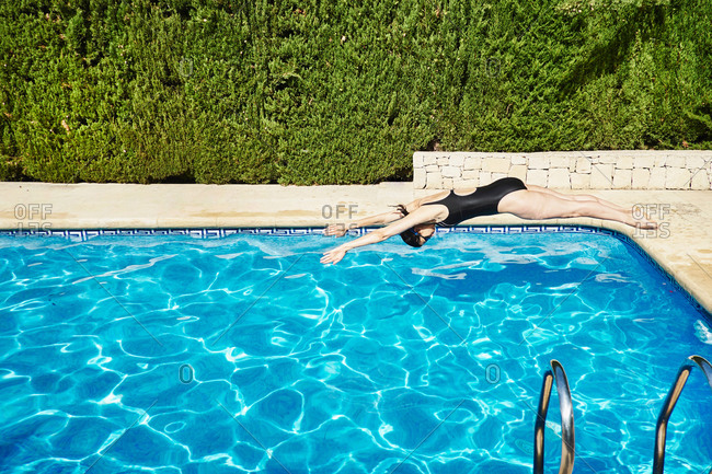 Mature woman diving into swimming pool
