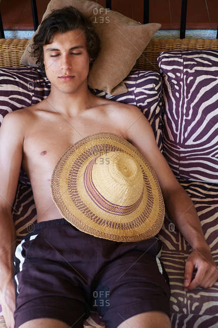 Young man lying on daybed with sunhat in stomach