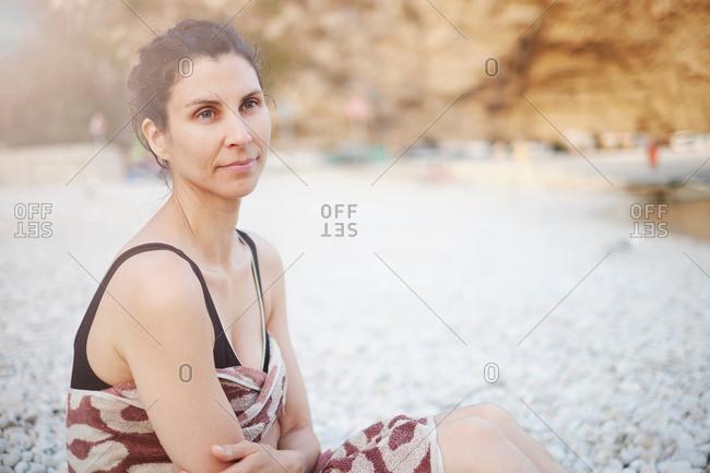 Mature woman sitting on beach, Javea, Spain