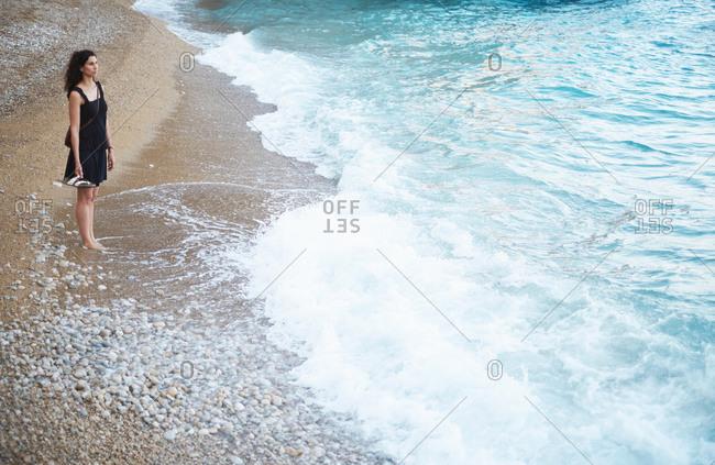 Teenage girl looking out from beach, Javea, Spain