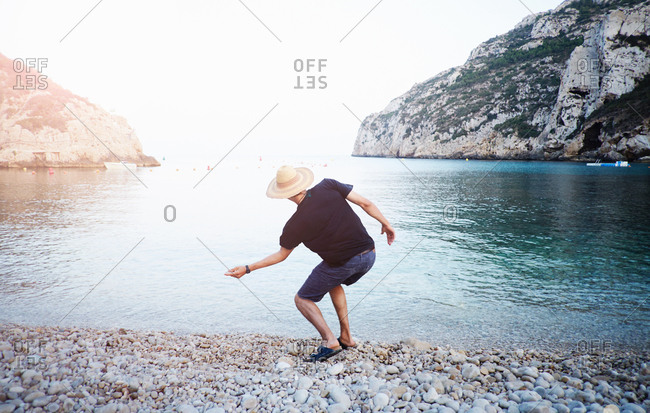 Rear view of young man skimming stones from beach, Javea, Spain
