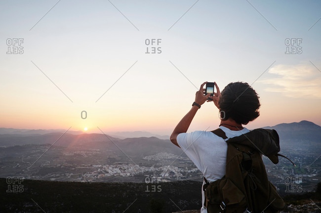 Rear view of young man photographing landscape and sunset on smartphone, Javea, Spain