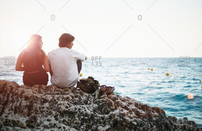 Rear view of young man and teenage sister on rocky beach, Javea, Spain