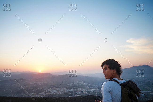 Young man looking out at landscape and sunset, Javea, Spain