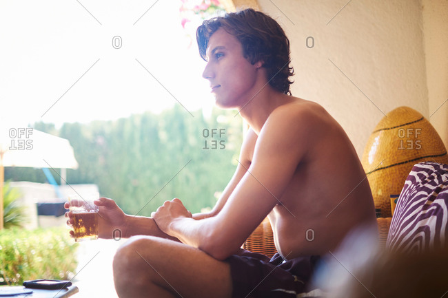 Young man sitting on patio chair drinking soft drink