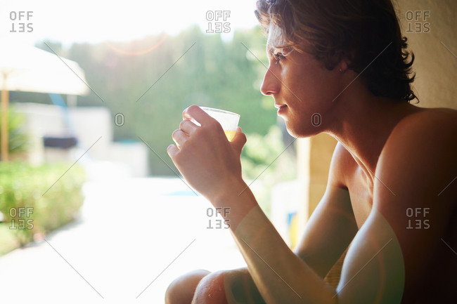 Young man drinking soft drink on patio chair