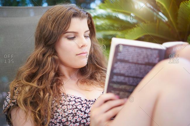 Teenage girl sitting on sun lounger reading book