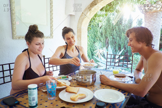 Mature woman with son and daughter eating lunch on vacation apartment patio