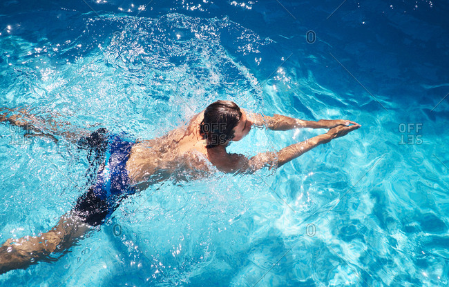 Overhead view of young man swimming in swimming pool