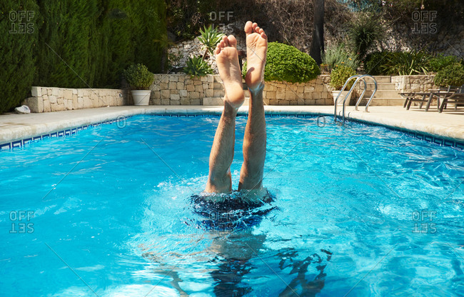Legs and feet of young man upside down in swimming pool