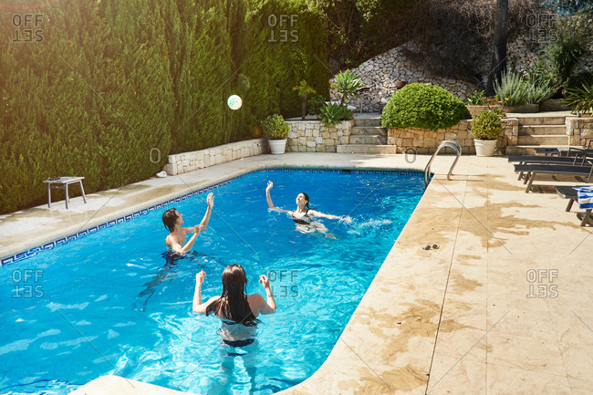 Mature woman throwing ball with son and daughter in swimming pool