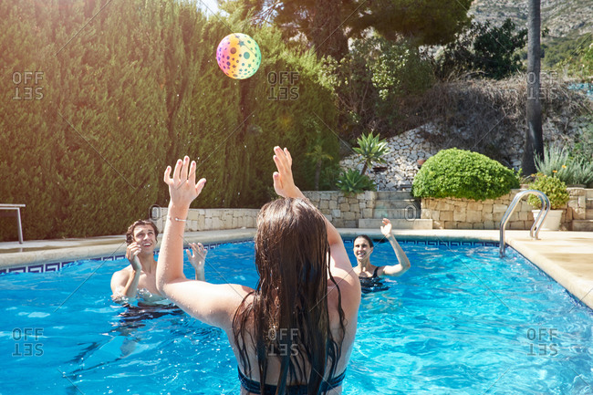 Teenage girl throwing ball to mother and brother in swimming pool