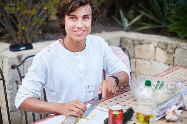 Young man slicing bread at patio table