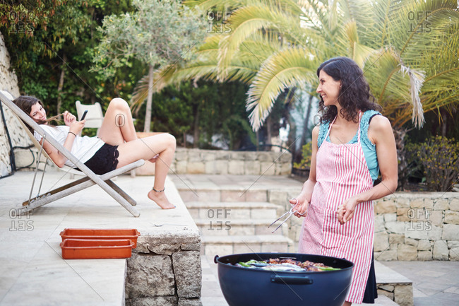 Mature woman preparing barbecued food for teenage daughter on patio