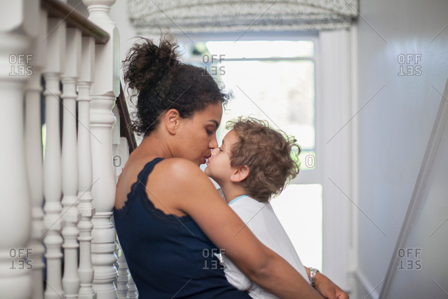 Mother and son sitting on stairs, son kissing mother