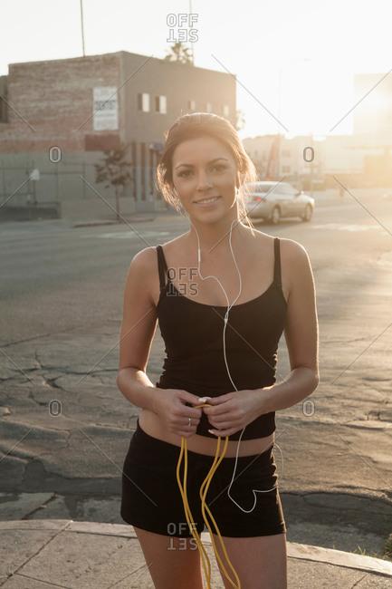 Portrait of young woman, wearing earphones, wearing sportswear